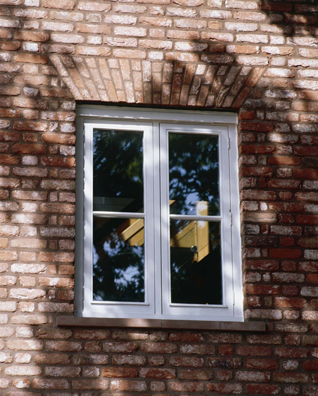 white timber casement window in brickwork with flat segmental arch