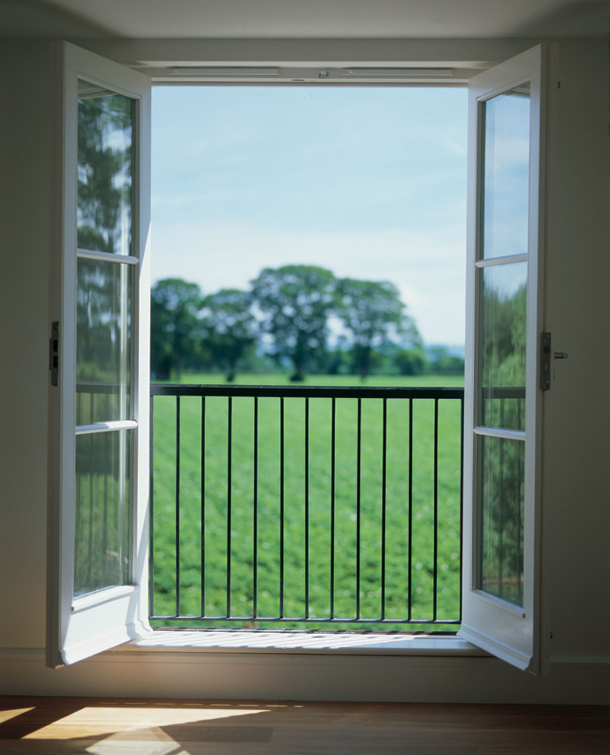 green fields through open timber casement window sunshine