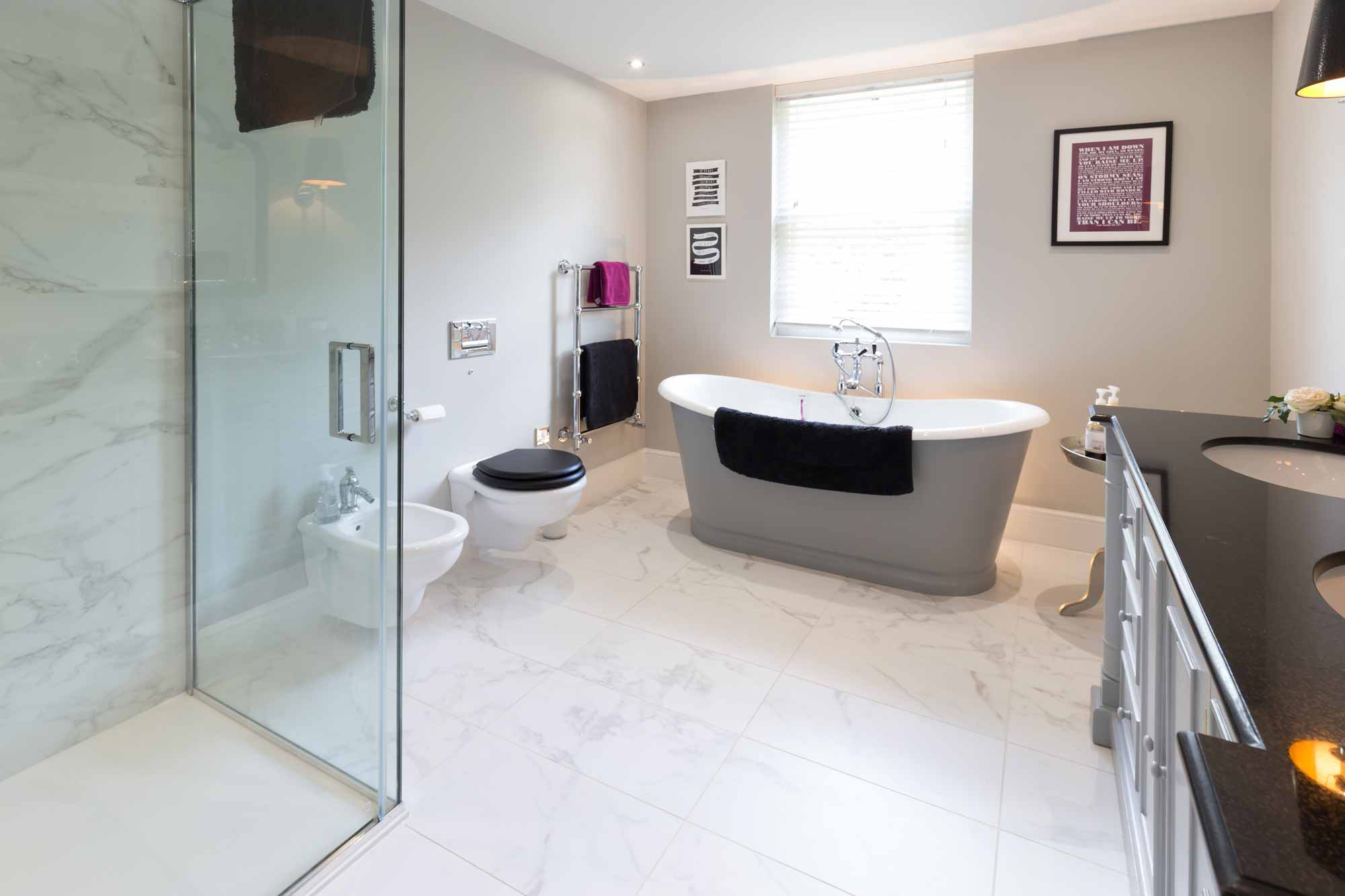 role top bath, his and hers sink, vanity unit, wall hung WC and bidet, glass shower