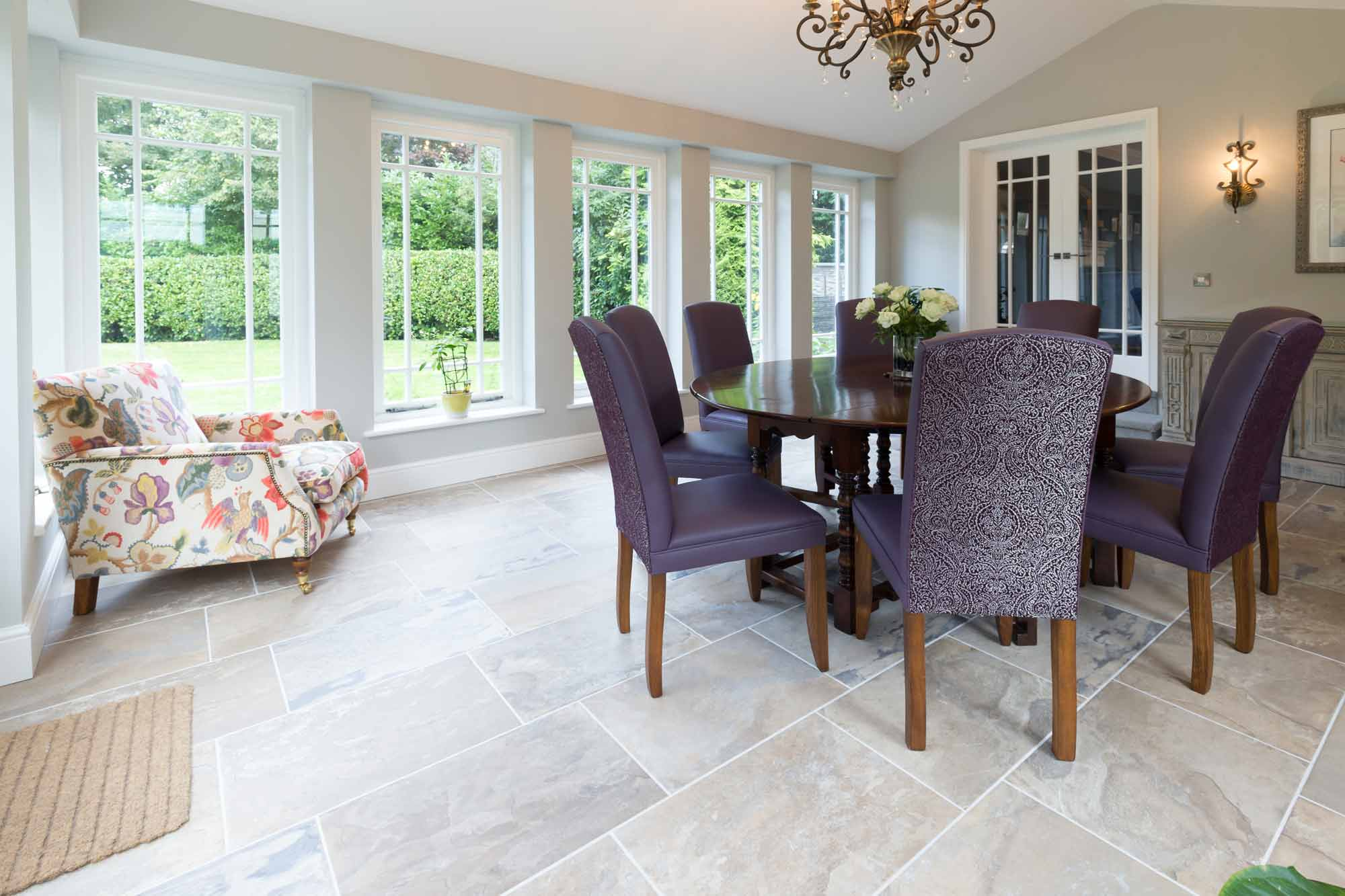 dining table and chairs, stone flooring, chandelier, orangery glazing, garden room