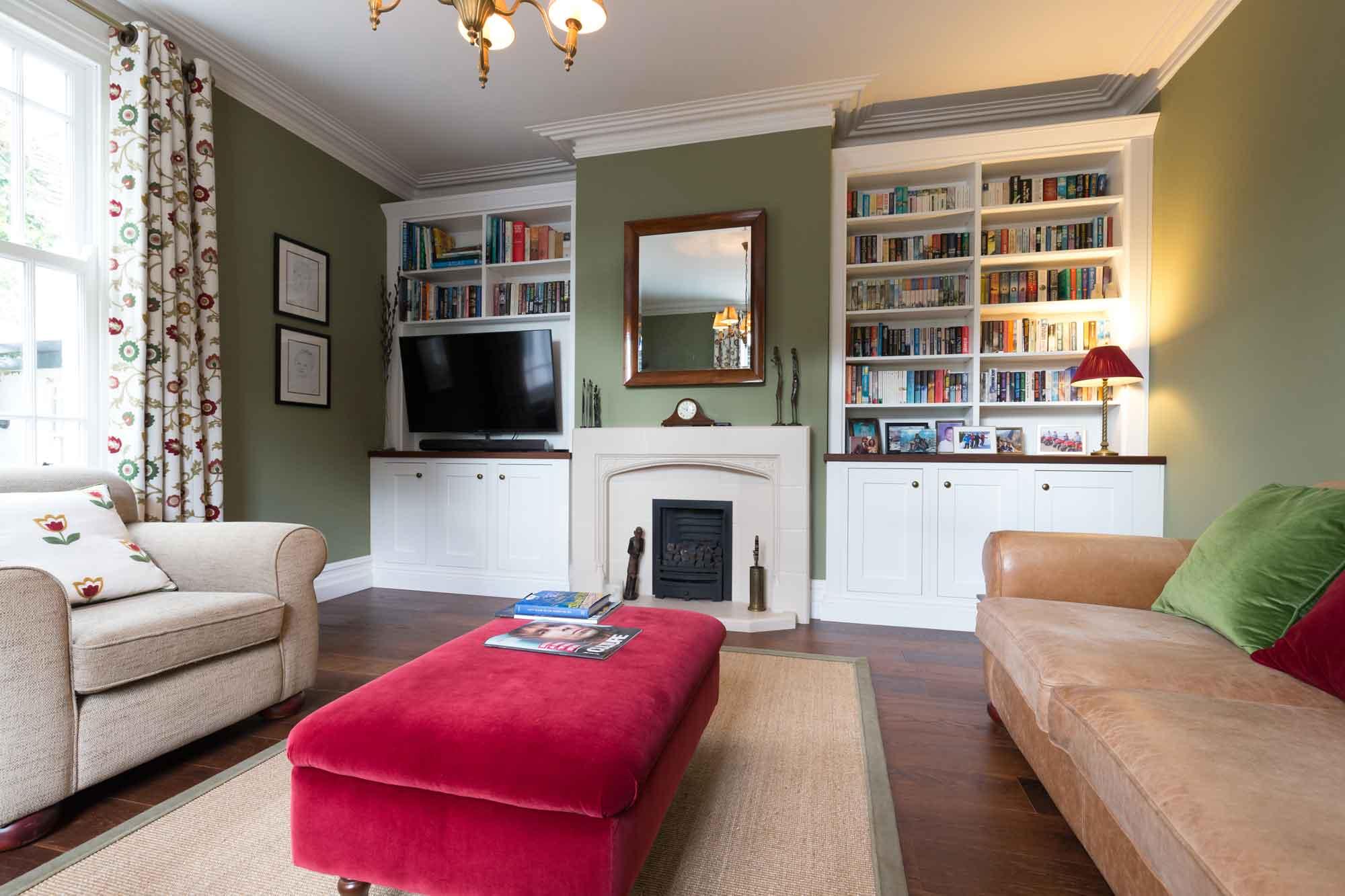 hardwood flooring, fireplace, bookcase, cornice, sofa