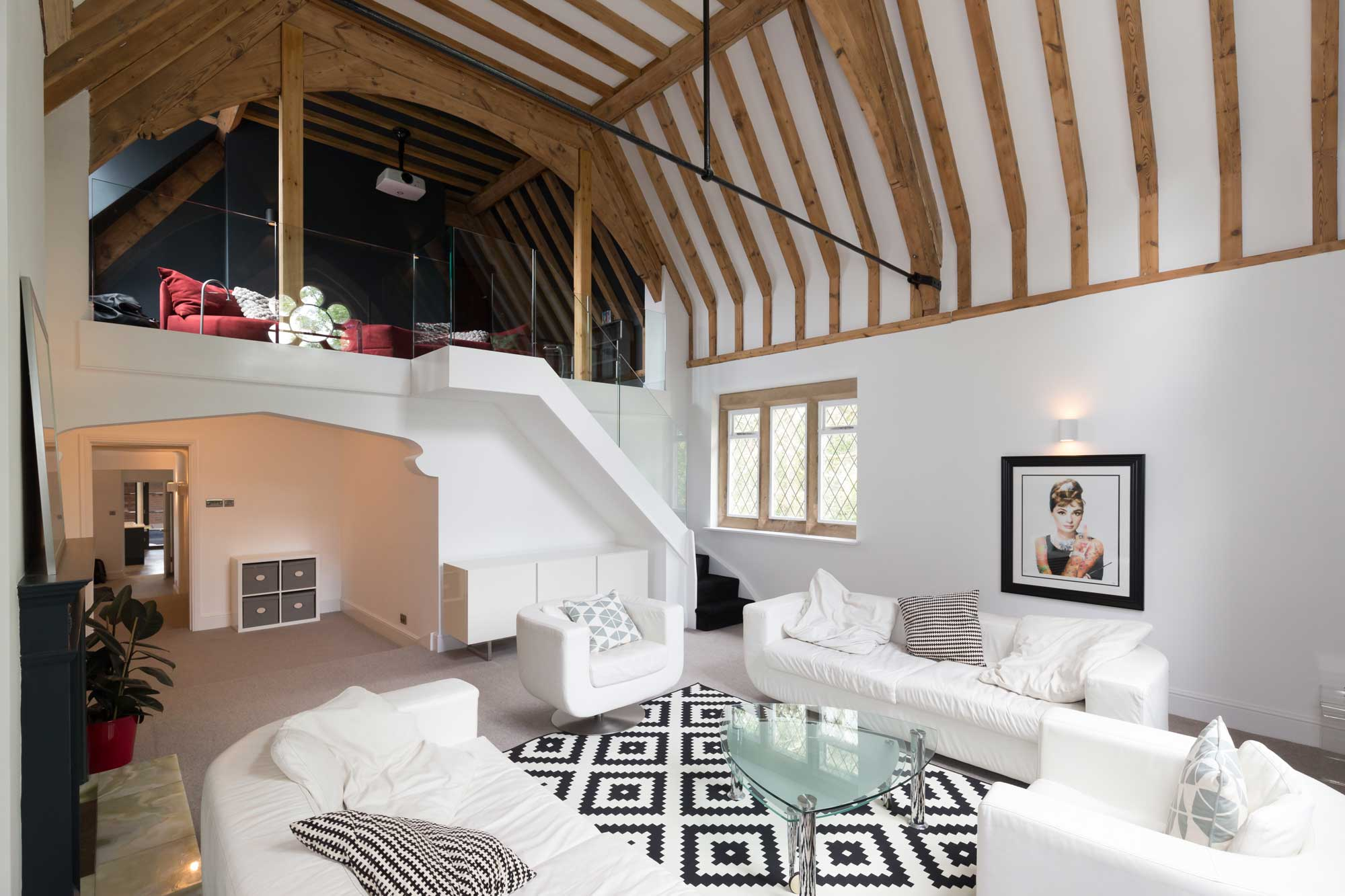 double height lounge vaulted ceiling exposed timber rafters vaulted ceiling, frameless glass staircase, floating stair, cinema room, balcony