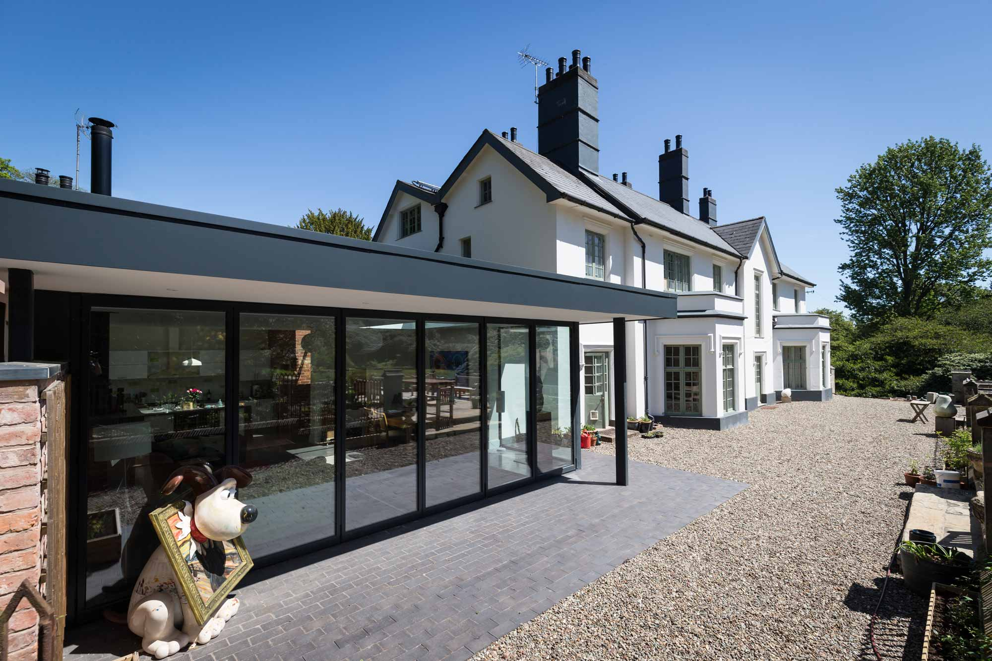 flat roof single storey extension with aluminium fascia and full height bi-fold doors onto patio with overhanging roof extension to a country house in Baldwins Gate