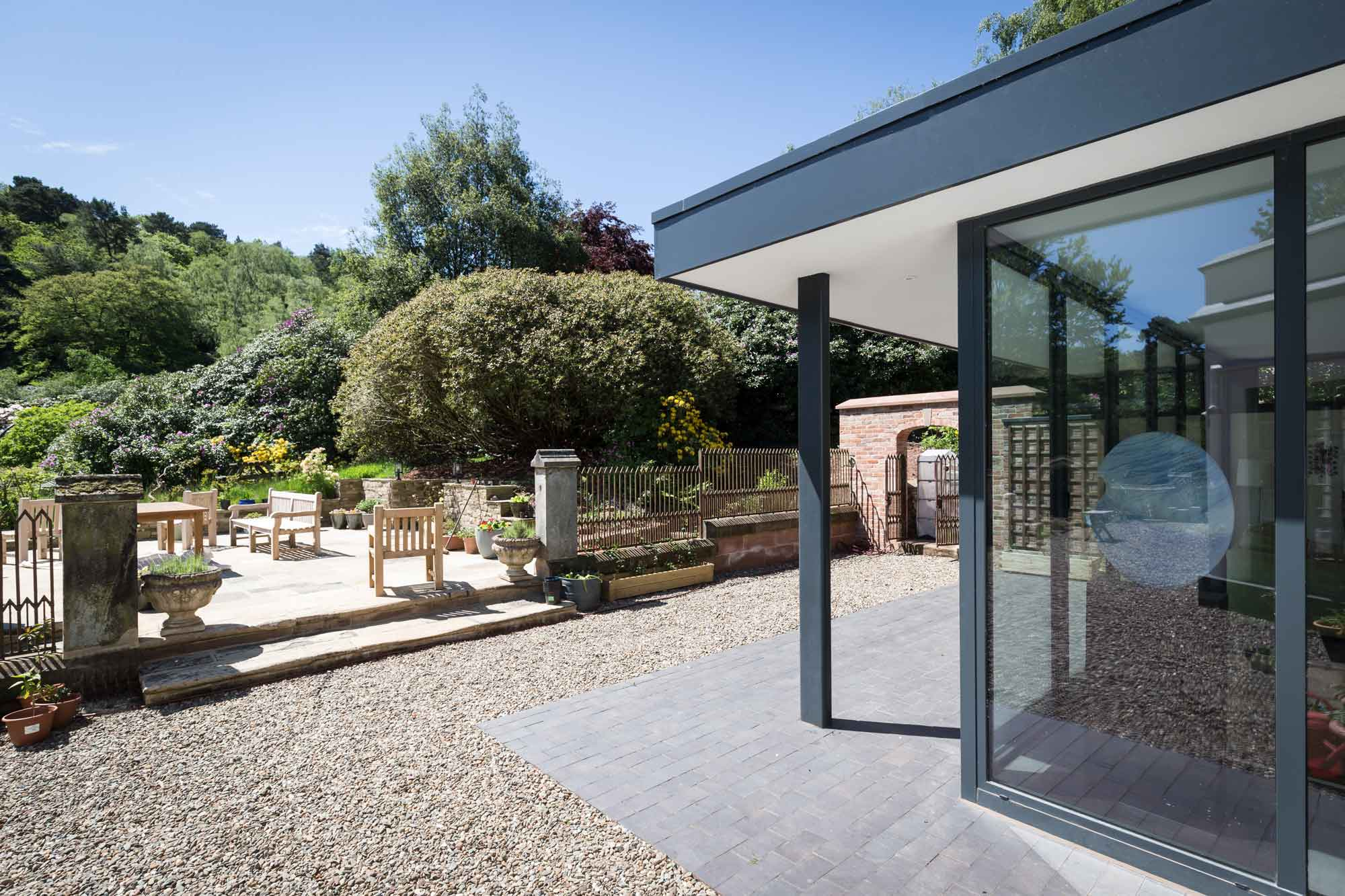 view toward garden and grounds with rendered soffit overhanging roof, aluminium fascias and full height aluminium bi-folding doors extension to a country house in Baldwins Gate